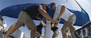 men hoisting sail on yacht